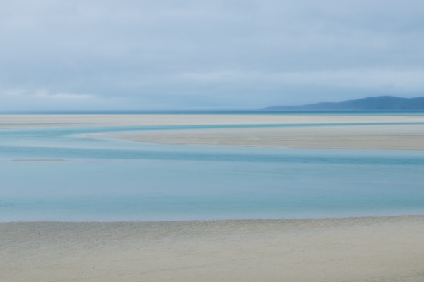 looking across to the island of Taransay in evening light and the tide is out