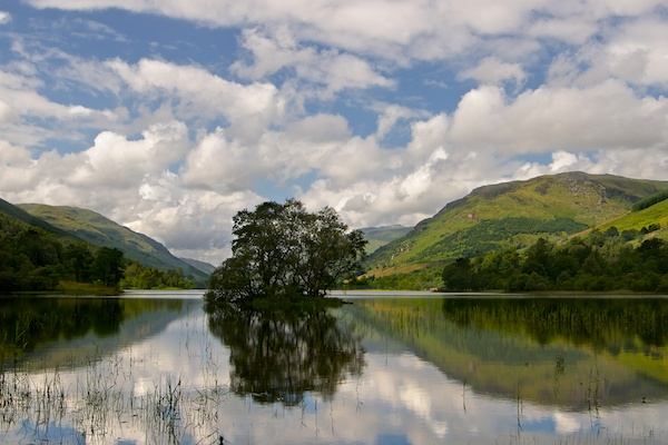 Loch Voil with island of trees and reflections of the surrounding mountains.