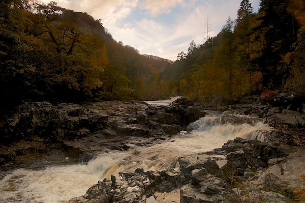 The waterfall emerges out of an autumn tree lined river Tummel