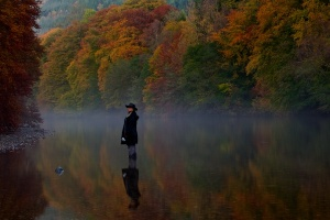 A women stands in the River Garry wearing a hat amidst autumn coloured trees on either side.