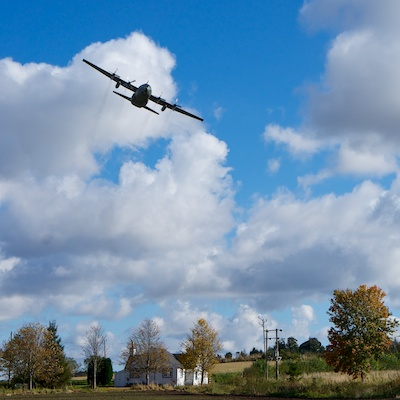 Hercules plane flys low over house