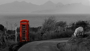 A remote phone box is in red in an otherwise black and white image of a road and sheep and the sea with the islands of Rum and Eigg in the distance.