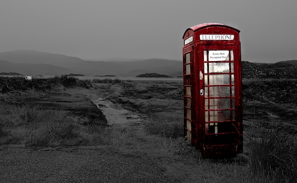 A remote telephone box is shown in red in an otherwise black and white landscape
