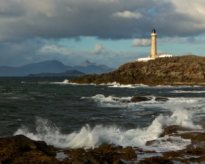 Ardnamurchan point lighthouse from across a bay showing waves coming in and the Ilses of Eigg and Rum in the background