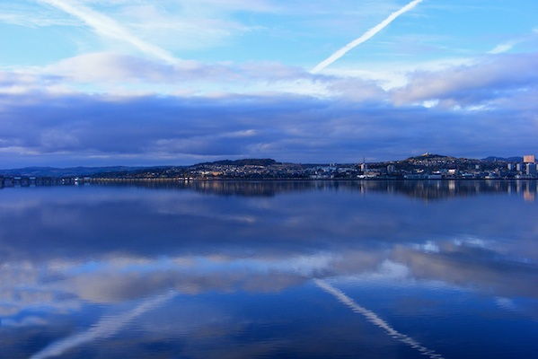 White clouds in a v shaped form a reflection in the river Tay to look like a St Andrews cross over Dundee