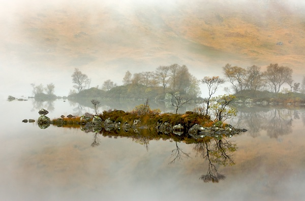 misty loch scene with a sall island standing out and its reflection also seen in the water
