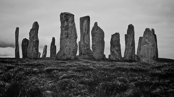 standing stones across the top of a hill in black and white and heavt cloud in the background