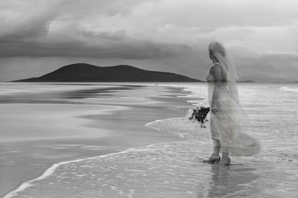 bride is a ghostly see through image on a beach with a hill on the distant shore