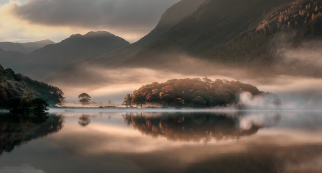 the misty water of Crummock Water, driving the mist away and filling the shadows with warm light.