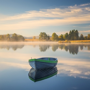 a boat sits on a loch which reflects a blue sky and is perfectly still