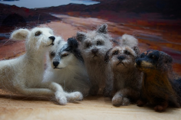 five dogs made from needle felted wool sit in  a row.