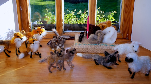Range of felted animals (foxes,sheep,dogs,hares) and the  tools and material at the back, which consists of a sponge pad and a needle holder that allows three needles to felt the wool at a the.