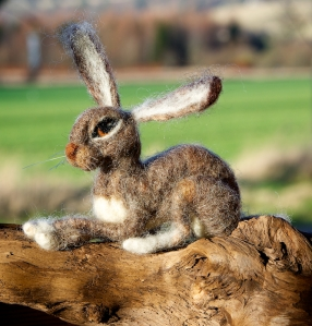 A felted Hare sitting on a small log.