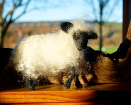 A white sheep with a black face made from felt sitting on a window sill.