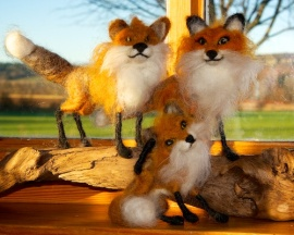 Three felted foxes in a group. Two are at the back standing on a log.