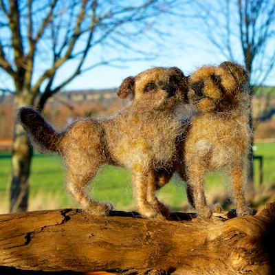 Tow felt sculptures of border terriers standing together on part of a log.