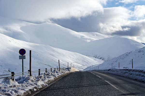 Road looking down through snow covered mountains.