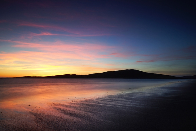 orange from the sunset is reflected on the sand and over the sea to the call island of Taransay in the distance