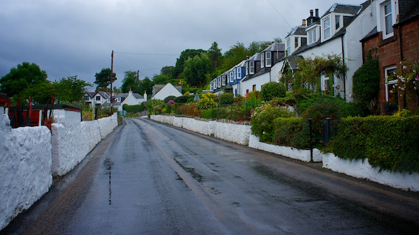 Row of houses all painted white with flower fled front gardens and a white wall along side a wet road running through.