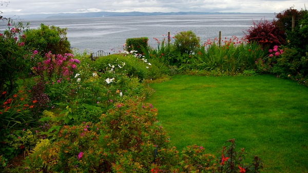 Small garden with floral borders and agate at the far side leading on the a beach and a view out to sea.