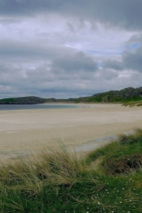 Looking across a large beach. Grass in the foreground