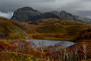 A dark grey mountain cover the top third of the picture with a loch and some trees in front.