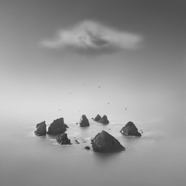 Rocks energy from a calm sea in a greys cal black and white image , there is a mysterious cloud snap just above the rocks