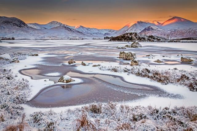 Fristy winter scene of a loch with SCottish Mountins in the distance and a red sunrise coming over them.