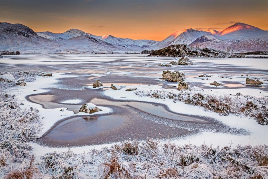 Frosty winter scene of a loch with SCottish Mountins in the distance and a red sunrise coming over them.