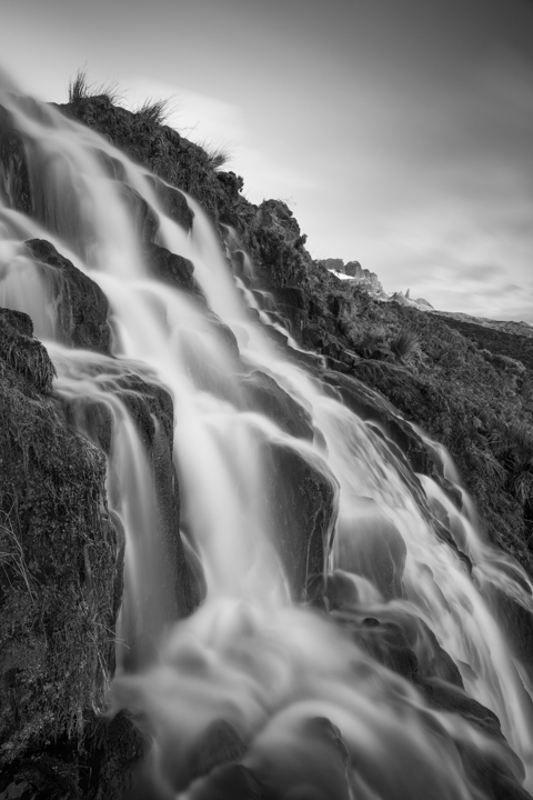 A waterfall in slow motion and behind it in the distance the pointed structure of the old man of store mountain on Skye